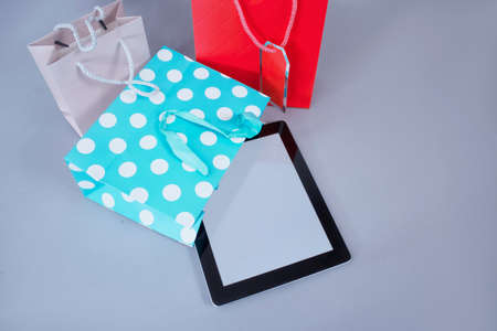 Online shopping concept. Close-up tablet mockup with white screen with bright gift bags on gray background 免版税图像 - 153568834
