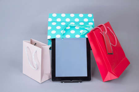 Online shopping concept. Close-up tablet mockup with white screen with bright gift bags on gray background