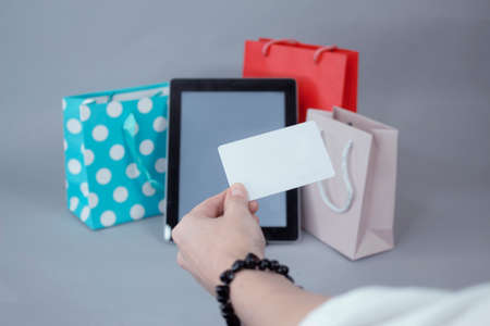 Online shopping concept. A girl holds a credit card in her hands, against the background of a tablet mockup with a white screen and beautiful gift bags Banco de Imagens