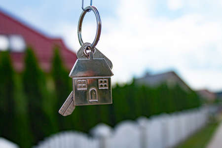 Metal keys to a new house on the background of residential buildings. Concept for buying and renting apartments.