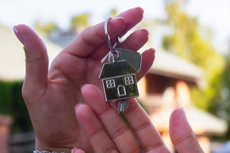 A woman holds in her hands the keys to the house against the background of residential buildings. Concept for buying and renting apartments.