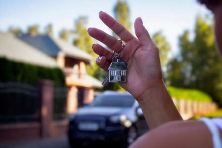 A woman holds in her hands the keys to the house against the background of residential buildings and cars. Concept for buying and renting apartments.
