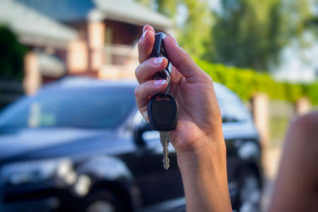 Woman holds the car keys. Concept on the topic of buying and renting a automobile.