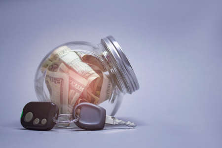 Glass piggy bank with dollars and car keys on a light background with shiny effect. Money set aside to buy a car. Banco de Imagens