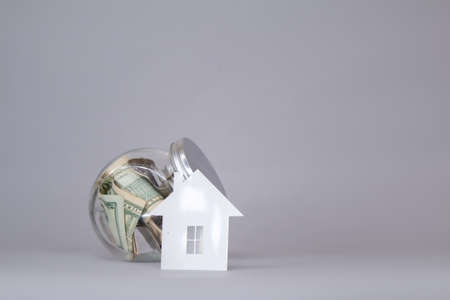 Glass piggy bank with dollars and on a gray background. Money set aside to rent and purchase of a house.