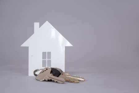 Home keys on a gray background with paper House.
