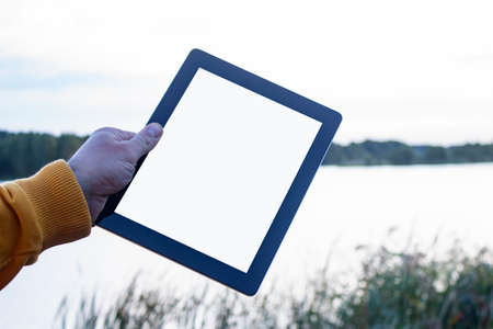 Mock up image of a Man holding black tablet in hand with blank white screen on background river.