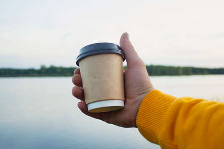 Man holds a cup of coffee in his hands on the background of nature with a lake.