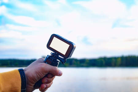 Tourist shoots a video on an action camera against the backdrop of nature and the river. Close-up of a white screen mockup on the camera. 免版税图像 - 157586856