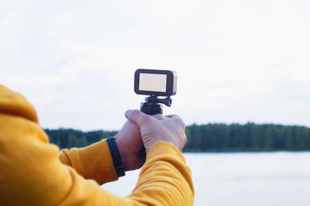 Tourist shoots a video on an action camera against the backdrop of nature and the river. Close-up of a white screen mockup on the camera.