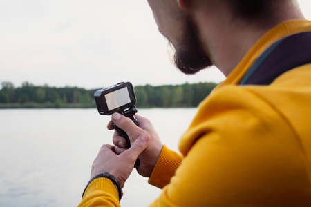 Videographer shoots a video about nature against the background of a forest and a river. A compact action camera with a white display mockup in the hands of a man. 免版税图像 - 157586858