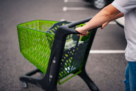 Man with a supermarket trolley in a parking lot against the background of a parking lot. Banco de Imagens