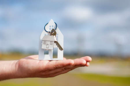 Guy holds the house keys in his hands against the background of clouds. Concept on the topic of buying a new home