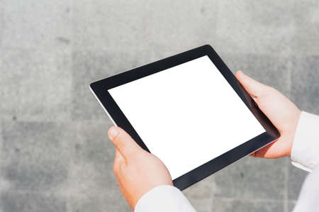 Close-up tablet mockup with a white screen in the hands of a businessman against the background of a concrete wall