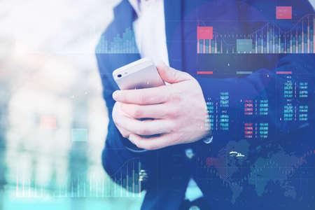 Business analytics with key performance indicators dashboard concept. Businessman in a blue jacket holds a smartphone in his hands