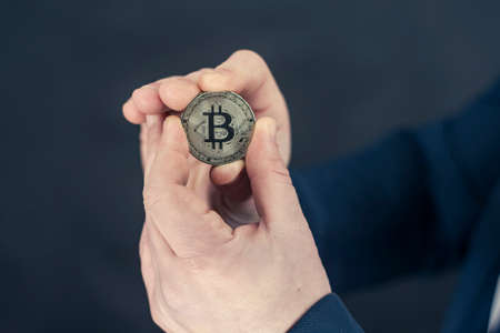 A businessman in a blue jacket holding Bitcoin in his hands. Virtual currency and blockchain concept