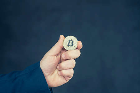 Virtual currency and blockchain concept. Businessman in a blue jacket holding Bitcoin in his hands 免版税图像