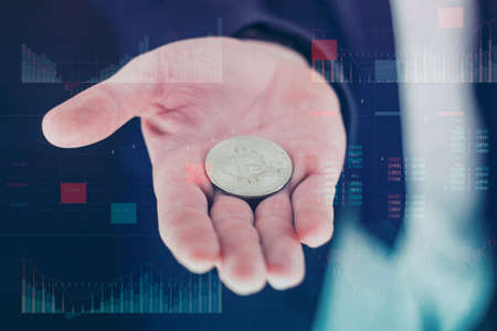 Businessman holds a gold bitcoin coin in his hands. Information holographic panel with statistics shows the fall and growth of the cryptocurrency. Virtual currency and blockchain concept
