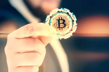 Businessman holds a gold bitcoin coin in his hands. Informational holographic panel with bright light effects. Virtual currency and blockchain concept