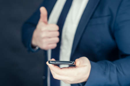 Businessman in a shirt and a blue jacket with smartphone in hand