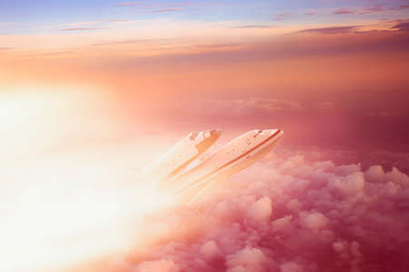 The plane transports a spaceship into space. Shuttle against the background of the sky with clouds and bright light