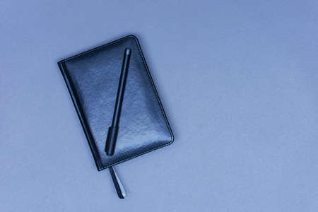 A closed black leather notebook lies on the table with a pen for notes