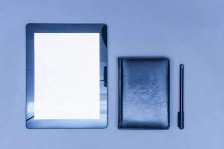 Mock-up of a tablet with a white screen lies on a table with a diary and a pen