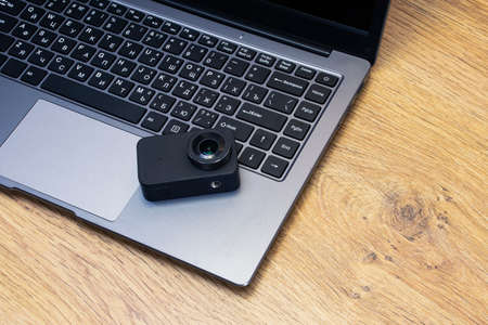 Compact action camera on the table against the background of the laptop
