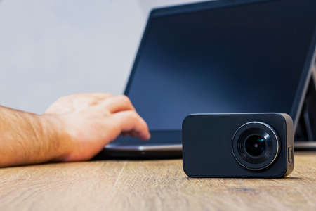 Action Camera on the table against the background of a man working at a laptop
