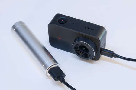 A compact action camera for shooting video and photos on a white background is charged from a power bank