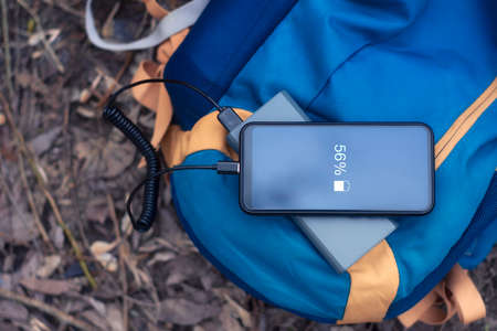 Smartphone is charged using a portable charger. Power Bank charges the phone outdoors with a backpack for tourism in nature