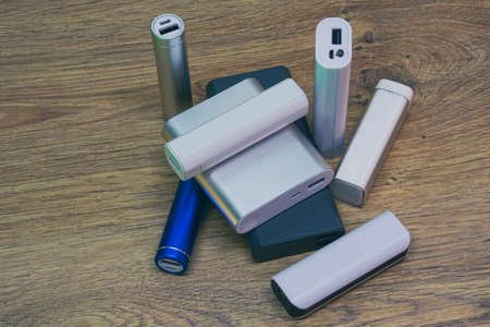 Set of power banks of different sizes on a wooden table. Choosing a portable charger Standard-Bild