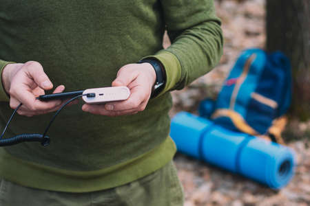 A man tourist holds a smartphone in his hands and charges it with a power bank. Backpack and a tourist rug in the forest