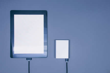 Portable charger charges a mockup Tablet with white screen isolated on a gray background