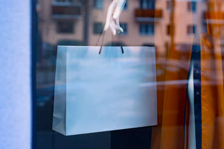 Mock-up of a white paper bag in the hands of a mannequin in a coat on a shop window