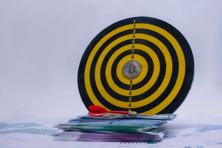 Concept of success and goal achievement. Round dart board with a bundle of dollars, euros and a bitcoin coin in the center of the circle against the background of graphs and diagrams on paper Standard-Bild