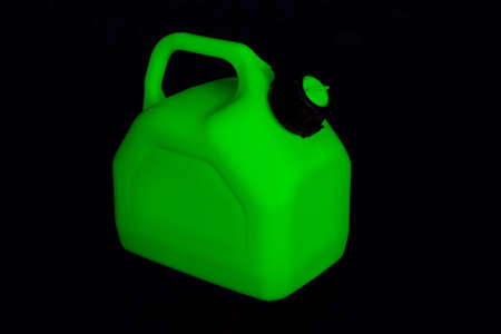 Mockup of a green plastic canister for car fuel on a black background. Container for liquids and hazardous fuels Standard-Bild