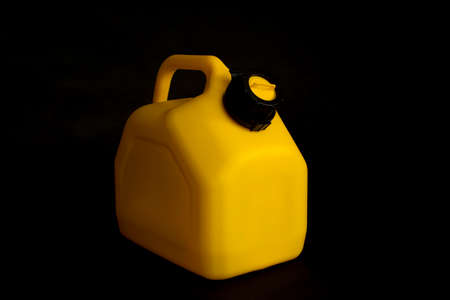 Mockup of a yellow plastic canister for car fuel on a black background. Container for liquids and hazardous fuels