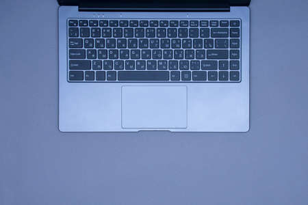 Open laptop with keyboard on a gray background. Top view
