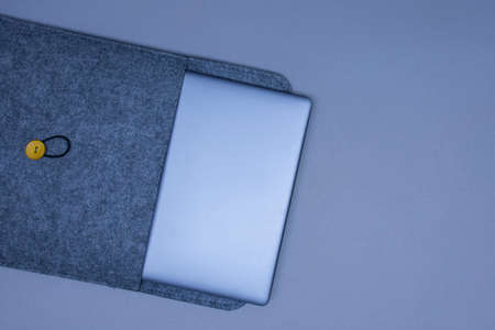 Closed silver laptop in a protective case on a gray background. Top view
