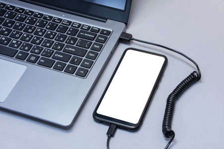 Mock-up of a smartphone with a white screen close-up being charged from a laptop on the background of a gray table