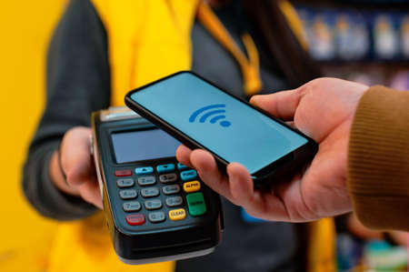 Customer is paying with smartphone in shop using NFC technology. against the background of the payment terminal and the seller's girl Standard-Bild