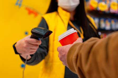A girl seller in a medical mask from a virus holds a barcode scanner in her hands. A man with a glass of coffee in his hand pays at the checkout