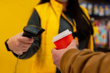 girl seller holds a barcode scanner in her hands and is counting on a man with a glass of coffee in his hand