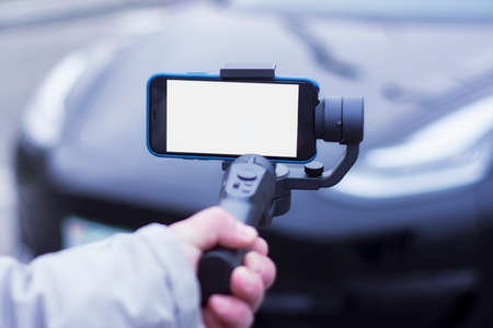 The blogger guy makes a video review of a modern car. A man holds a steadicam and a mock-up of a smartphone with a white screen in his hands