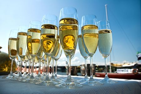 glasses filled with sparkling champagne at an outdoor party on a sunny day