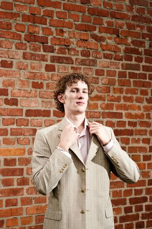 A handsome young man in a light-coloured suit posed against a brick wall, fixing his collar, looking confident