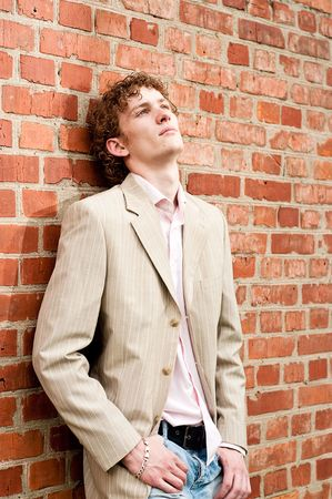 A handsome young man in a light-coloured suit posed against a brick wall, relaxed and dreamy, reflecting on his life