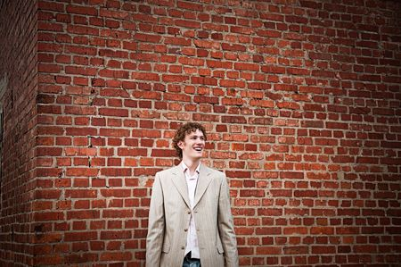 A handsome young man in a light-coloured suit posed against a brick wall, smiling friendly
