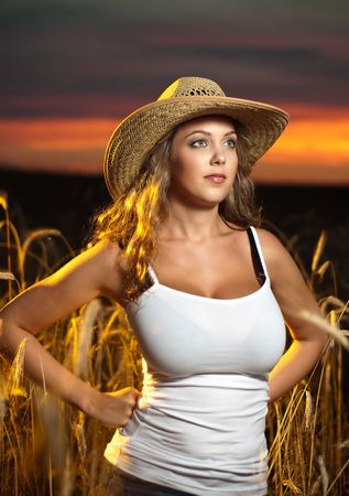 A lovely voluptuous young lady wearing a straw hat and a white tank standing in a field of wheat at sunset Stock Photo